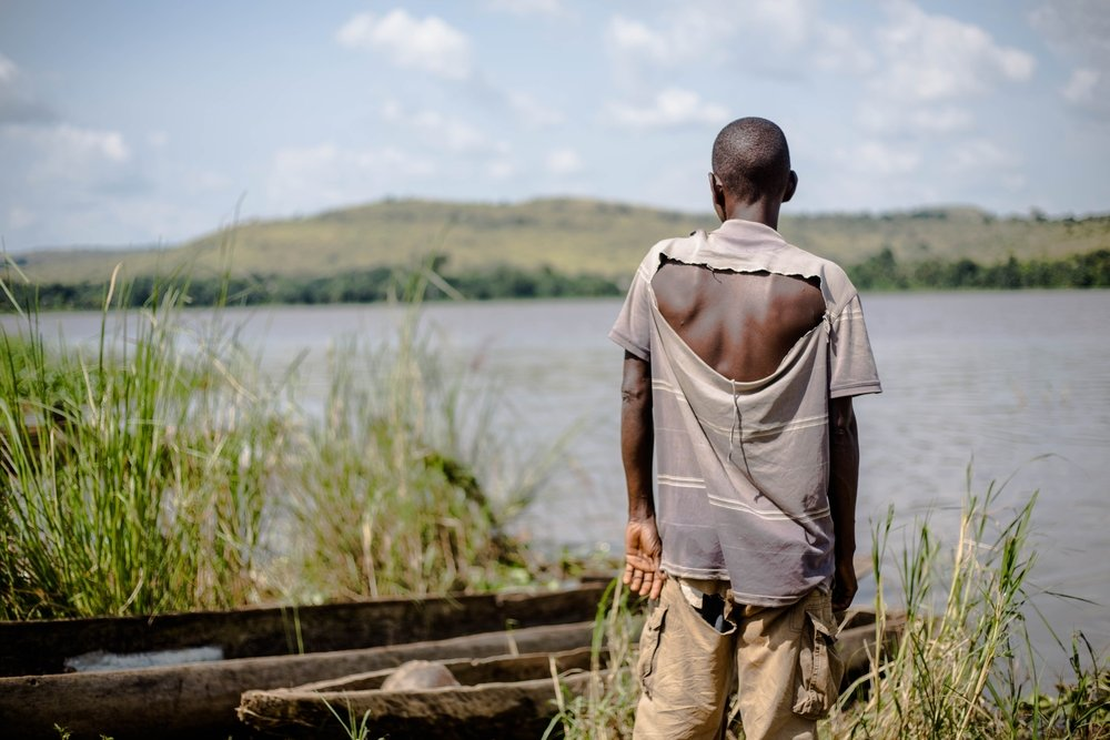 Fabrice Nzongba stares across the river to the village of Mobaye, where his son was killed