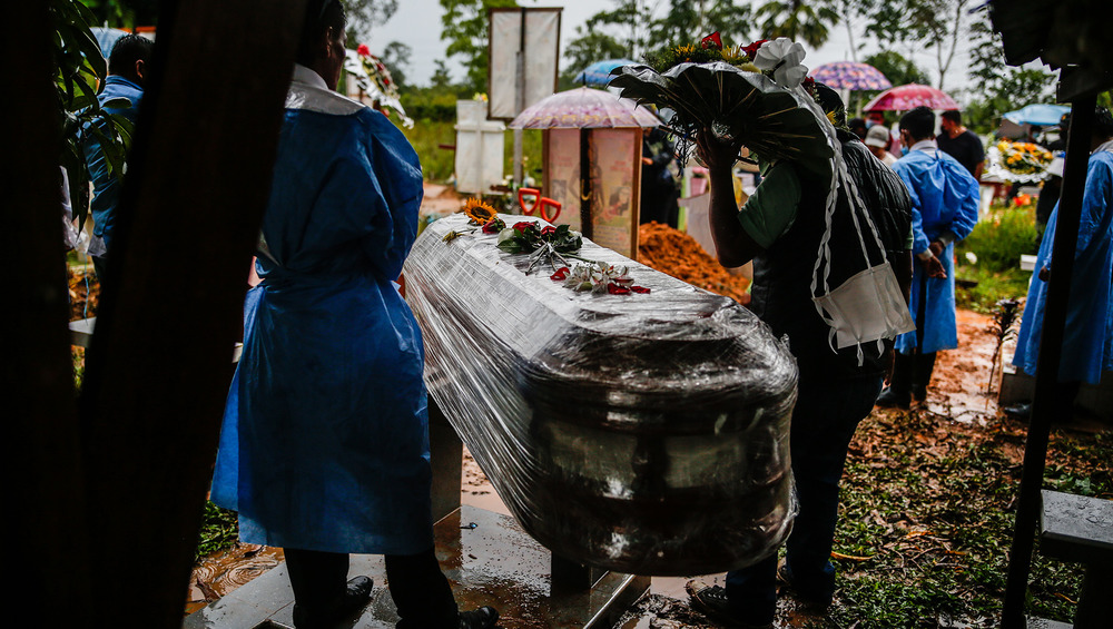 Several people hold up an adorned coffin in a cemetery.