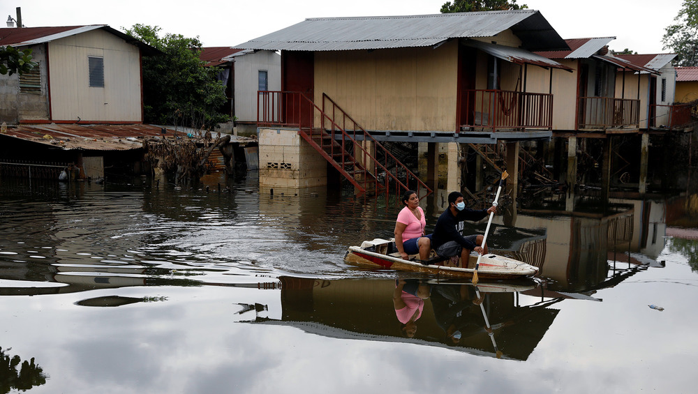 People travel through a flooded street on a jet ski hull, the houses in the background are submerged by floodwaters.