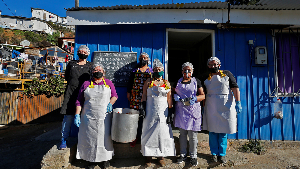 On a hill named 'Mariposas' ('Butterflies') in the Chilean city of Valparaiso, volunteers pose for a picture at an 'olla comun' – a communal kitchen set up to provide hot food for those with dwindling incomes or none at all