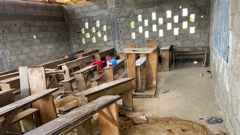 The photo shows a jumble of empty classroom pews with a few items of clothing and shoes strewn between them.
