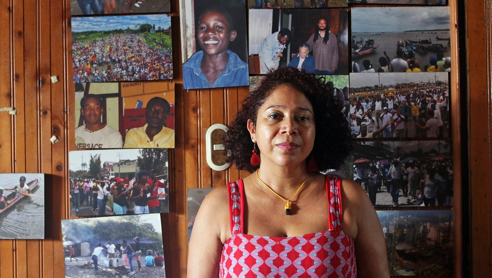 A portrait of  Danelly Estupiñán standing against a wooden wall decorated with photographs