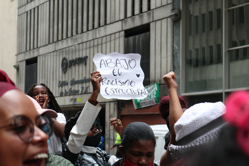 A girl holds a sign above her head at a protest on a street in Bogotá