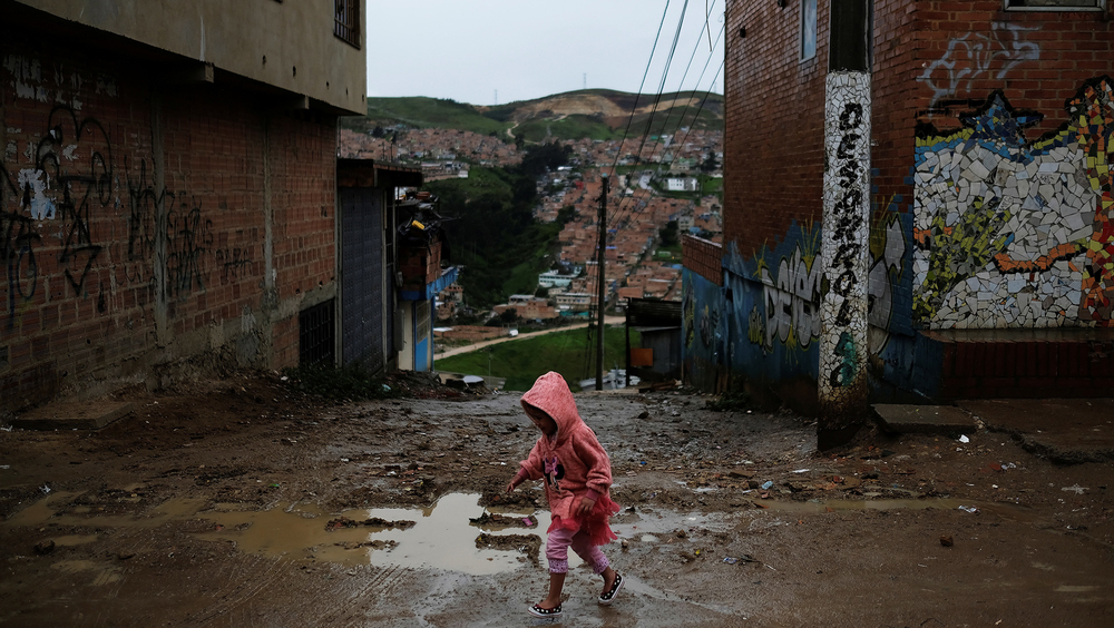A child walks on the street of a slum in Soacha, on the outskirts of Bogotá, Colombia