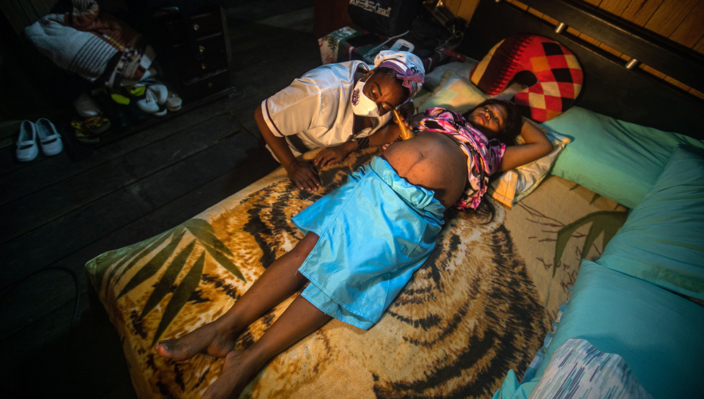 Juana del Carmen Martínez, a traditional midwife, assists an Indigenous mother, Elina Chamorro, by listening to her stomach as she lies on a bed, in Quibdó, Colombia, 29 November 2020.