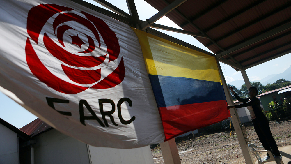 A woman hangs a Colombian flag next to a FARC political party flag