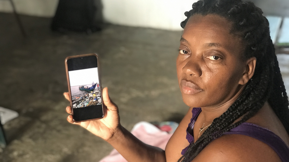 Nury Cabezas shows cell phone photos of displaced people