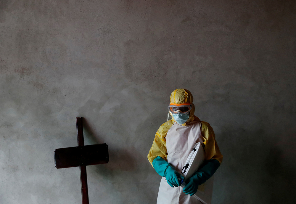 A healthcare worker stands next to a cross