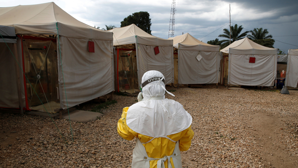 A health worker stands in the compound of an Ebola treatment centre in the eastern Congolese town of Beni. A report obtained by TNH has criticised efforts by aid agencies to contain the country's deadliest ever outbreak of the virus