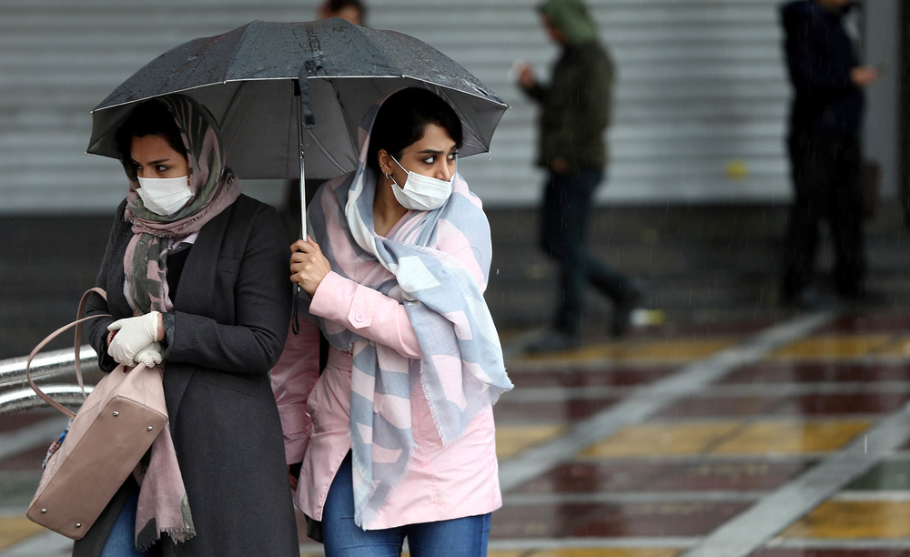 Iranian women wear protective masks to prevent contracting coronavirus as they walk in the street in Tehran.