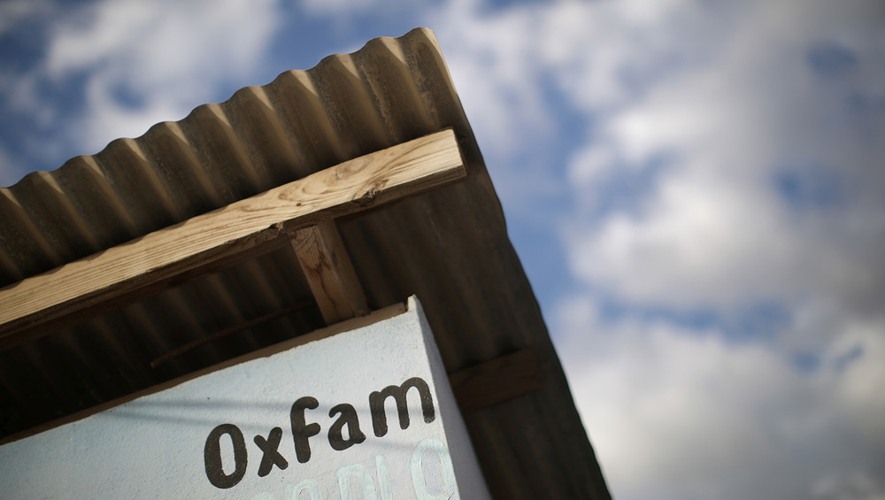An image of the word 'Oxfam' painted on the side of a building with a corrugated roof.