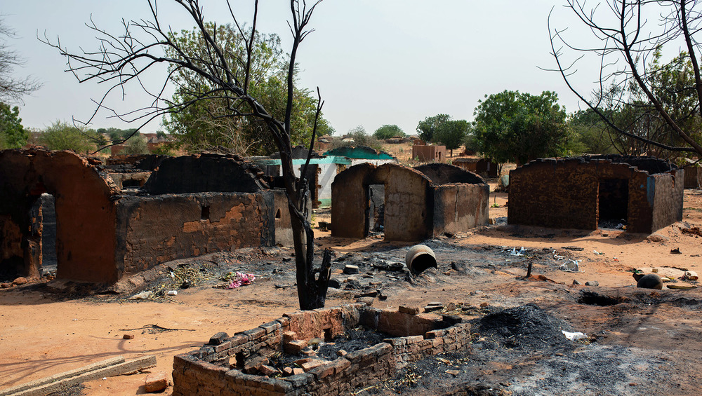 Multiple burnt dwellings stand empty in a dusty village.