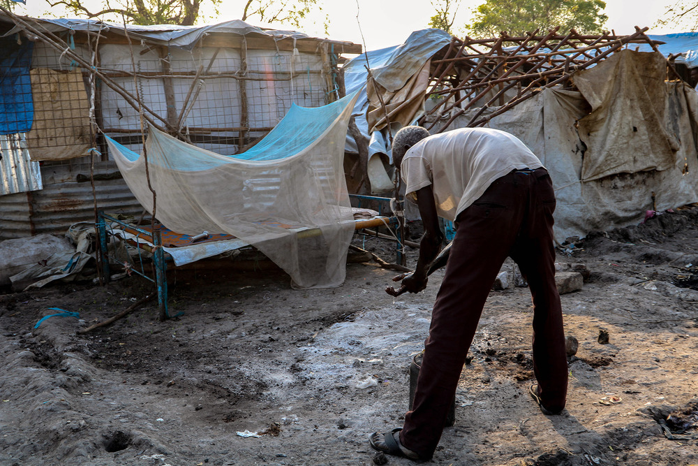 A displaced man with no shelter bends over a shallow bucket in a clearing between makeshift shelters.