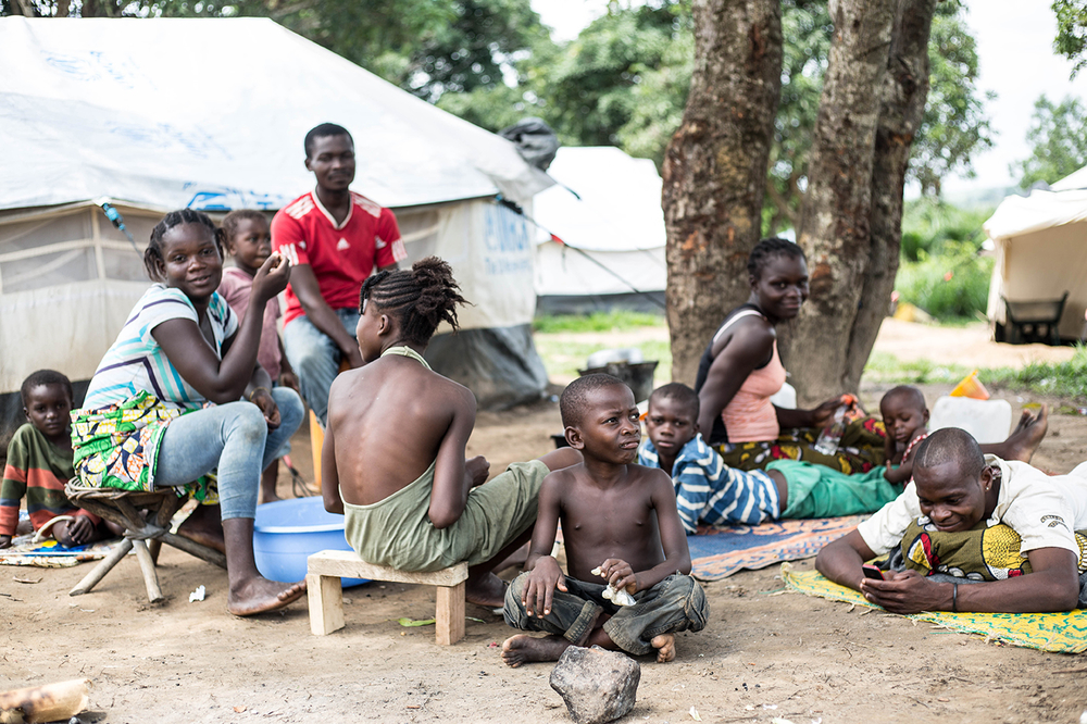 A group of people in Republic of Congo sit outside their temporary shelter in various positions some smiling