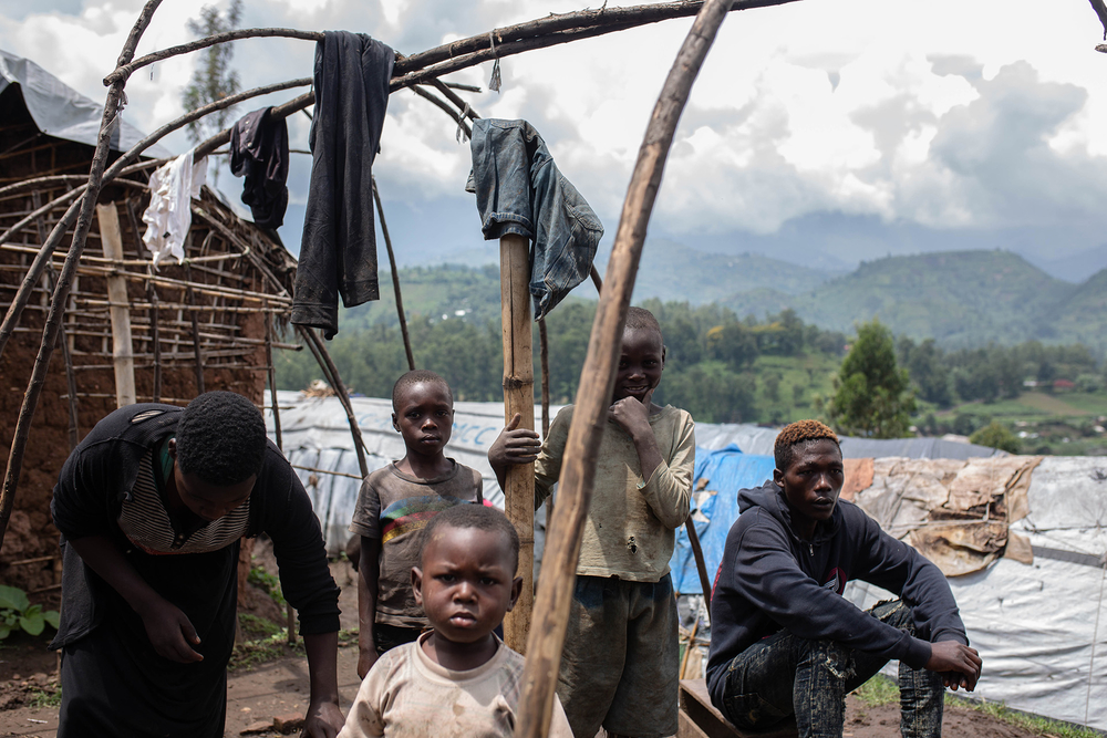 A family of internally displaced people build a new shelter at a camp in Minova