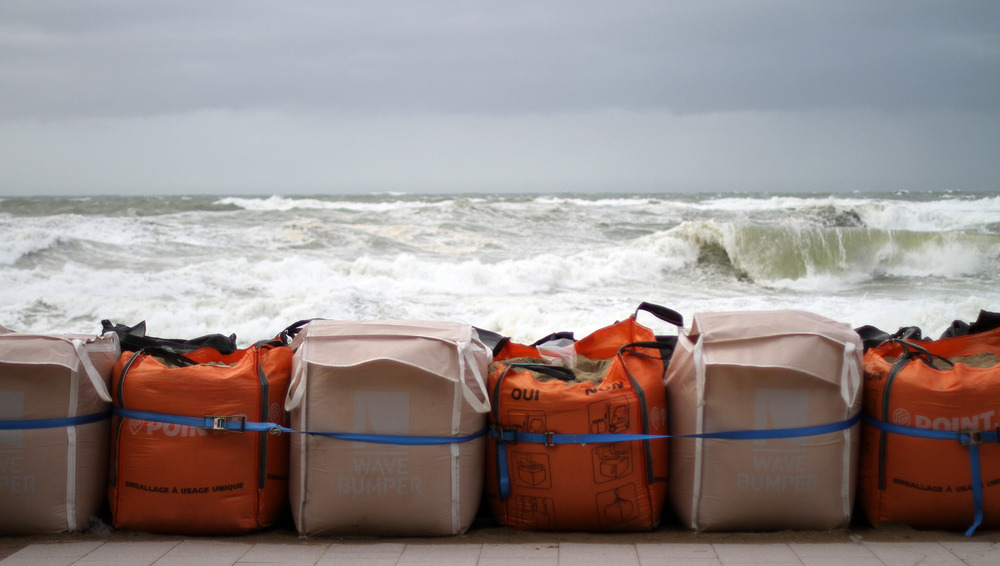 Waves roll towards a row of orange and beige sandbags.