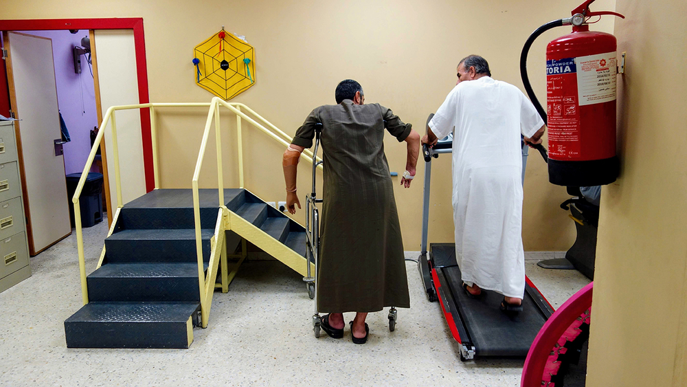 A man on crutches and a doctor in physical therapy