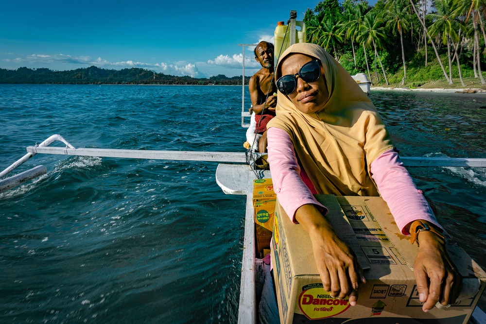 A woman with a headscarf and sunglasses on a boat carrying a box of aid on her lap