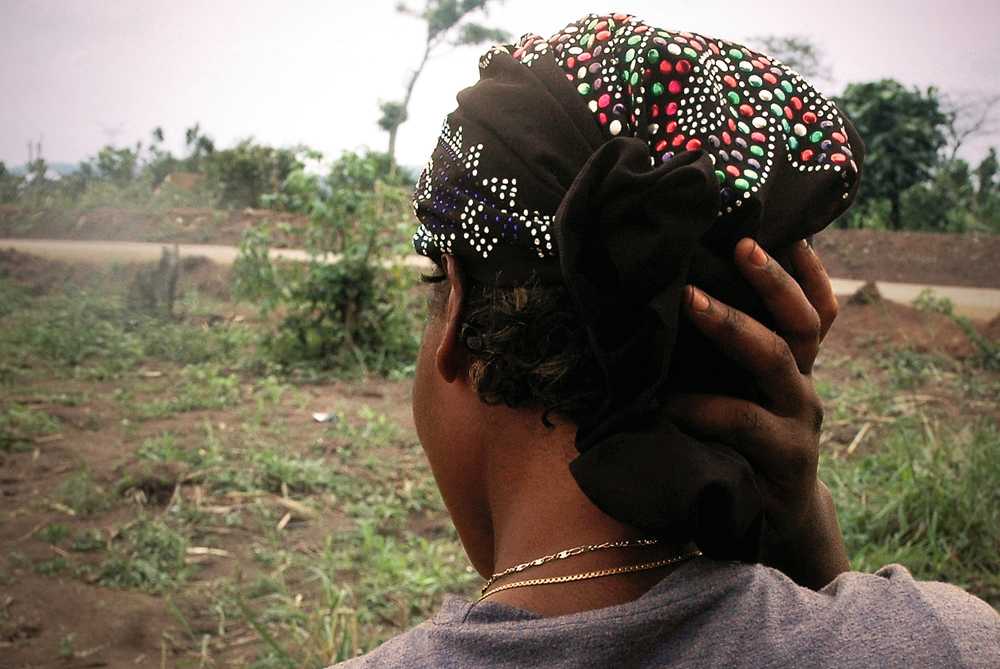 A portrait from behind of a Congolese rape survivor in a green field