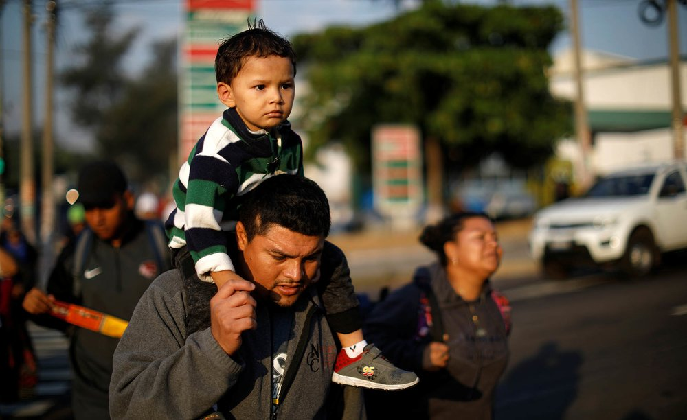 Father and son walk in a caravan of migrants en route to U.S. in San Salvador.