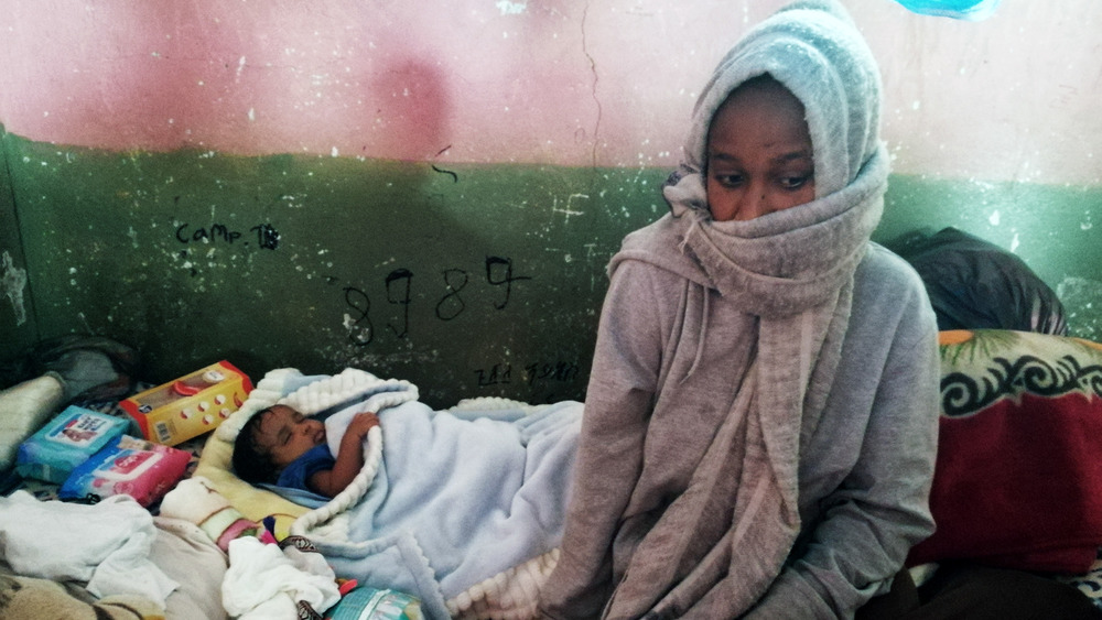 A mother sits in a makeshift shelter next to her sleeping child.