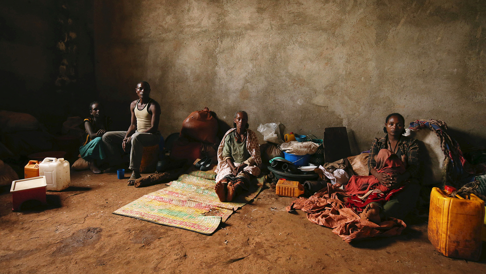 A family sits inside their shelter within a camp for internally displaced people in Chelelektu town of Southern Nations, Nationalities, and Peoples' Region (SNNPR) in Ethiopia, on 15 August, 2018