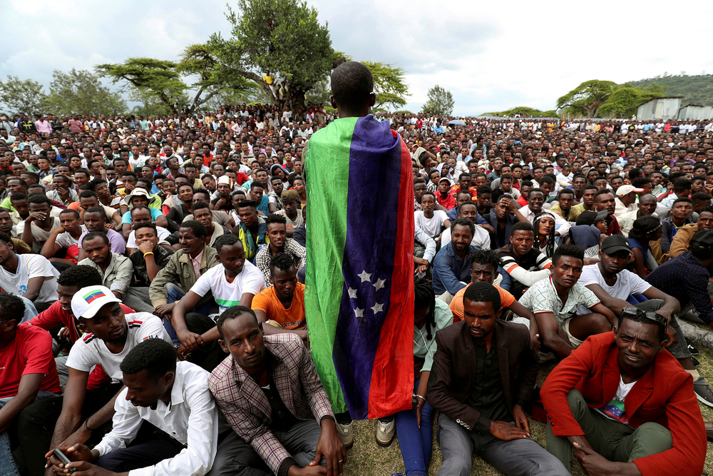 A Sidama youth leader carrying a flag addresses people as they gather for a meeting to declare their own region in Hawassa, Ethiopia.