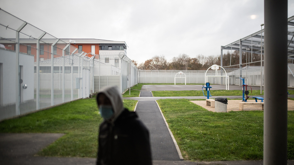 A young man stands in the courtyard of a centre near the French city of Rennes where migrants are detained before they are deported
