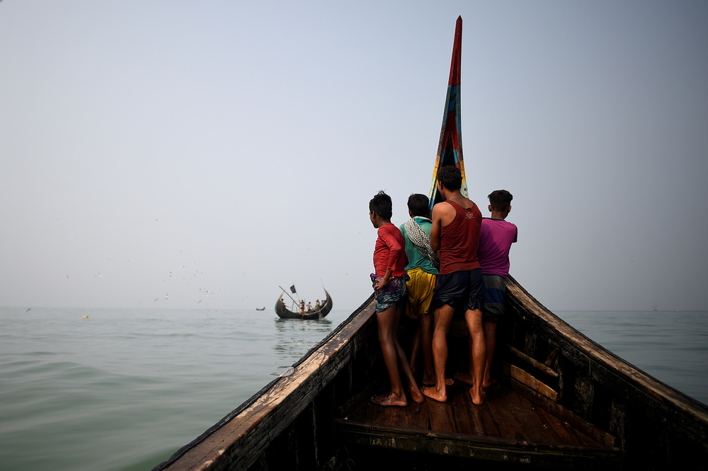 Rohingya refugees crew a fishing boat near Cox's Bazar
