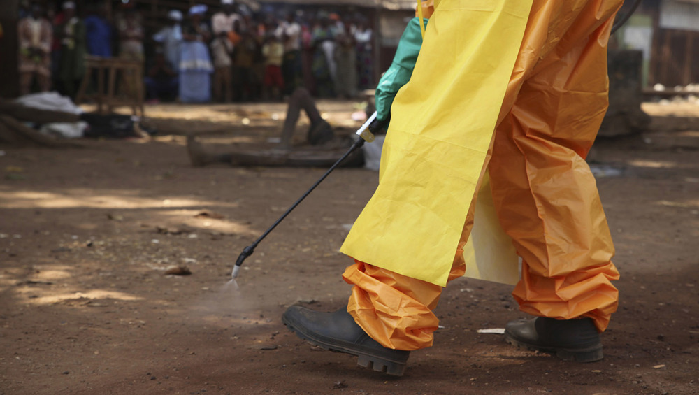 The image shows the bottom half of a person's body - dressed in a hazmat suit, apron, gloves, and boots - holding a disinfectant wand spraying the ground.