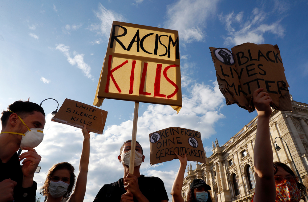 People hold signs during a protest against the police killing of George Floyd in Vienna