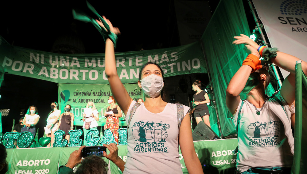 A demonstrator at a pro-abortion rally stands in front of a green banner cheering with one arm up.