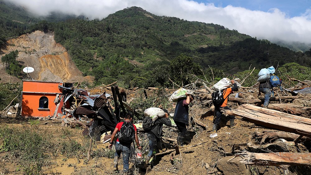 Residents carry belongings recovered from their houses, as the search for victims continues after a mudslide buried the village of Queja in Guatemala's Alta Verapaz department, on 8 November 2020.