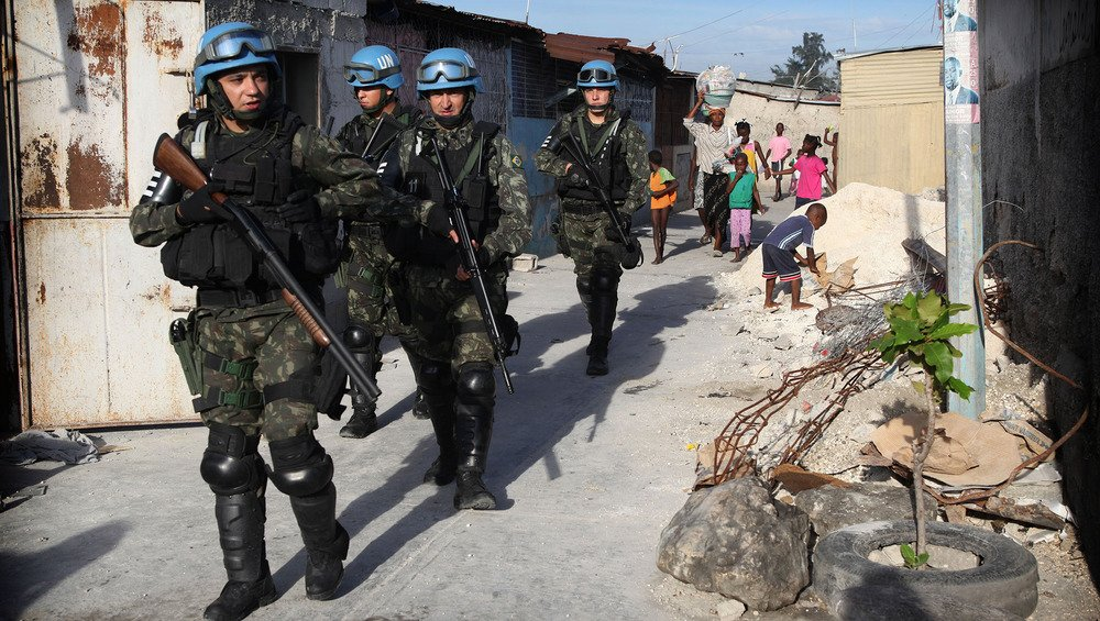 Several uniformed UN officers armed with guns make their way down a dusty street in a city settlement