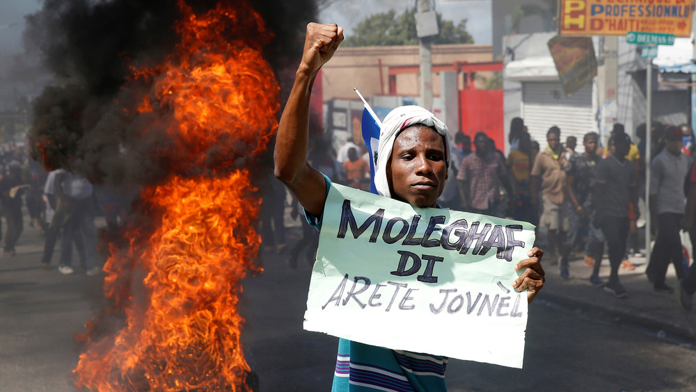 A young man holds a sign and stands in front of a fire on the street during a protest in Haiti