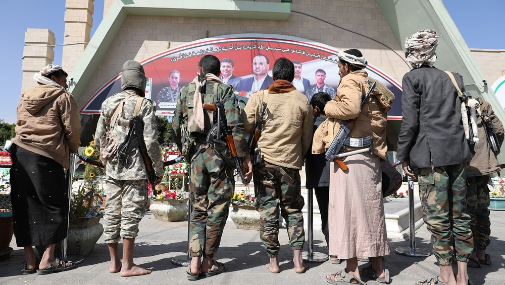 Armed members of the Houthi movement stand facing away from the camera outside the grave of senior official Saleh al-Sammad at al-Sabeen Square in Sana'a, Yemen, 11 January 2021