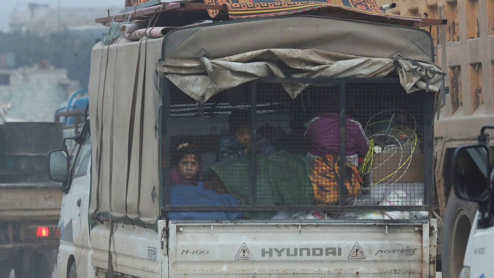 Displaced Syrian children sit at the back of a truck with belongings.