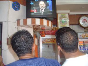 [Iraq] Patrons at local kebap house in Baghdad watch news of the handover on TV on Monday.