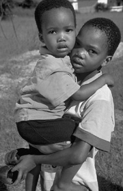 [Botswana] In Botswana, an 8-year-old boy holds his younger brother outside a drop-in center for orphaned children in the village of Molepolole, 50 kilometers west of Gaborone.