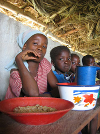 [Guinea] Local children eating bulgur on the way to Liberian refugee camp of Kountaya, Kissidougou area, Forest Region,June 12, 2004.