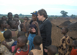 [Uganda] UNICEF Executive Director, Ann Veneman, talks to children displaced by war at Palenga IDP camp, near Gulu town. The chief mediator in thenorthern Uganda conflict, Betty Bigombe, is with her. 23 July 2005.