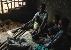 [Liberia] A family sits on what is their bed in a small mud hut in a Liberian IDP camp. The camp is bursting at the seams and the small mud huts cannot withstand the driving rains that hit Liberia in the rainy season. With no protection from the elements