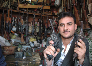 [Yemen] An arms merchant displays two old British revolvers, while modern Russian weapons hang on the wall of his shop. [Date picture taken: 2005/09/02]
