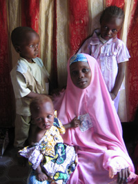 [Nigeria] Barahatu Kabiru poses for the camera in her best clothes with her three children. At her right shoulder stands Mustapha who had polio as a baby because his father prevented him from taking the polio vaccination. [Date picture taken: 08/23/2006]