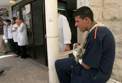 [OPT] A young man with broken arms looks at nurses who went on strike in Rafidea Hospital in Nablus. [Date picture taken: 08/28/2006]