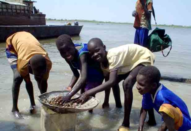 Children removing sand from the banks of the Nile, Malakal, Sudan, 16 February 2007. Many children do this kind of work to pay for school fees or to buy food and clothes.