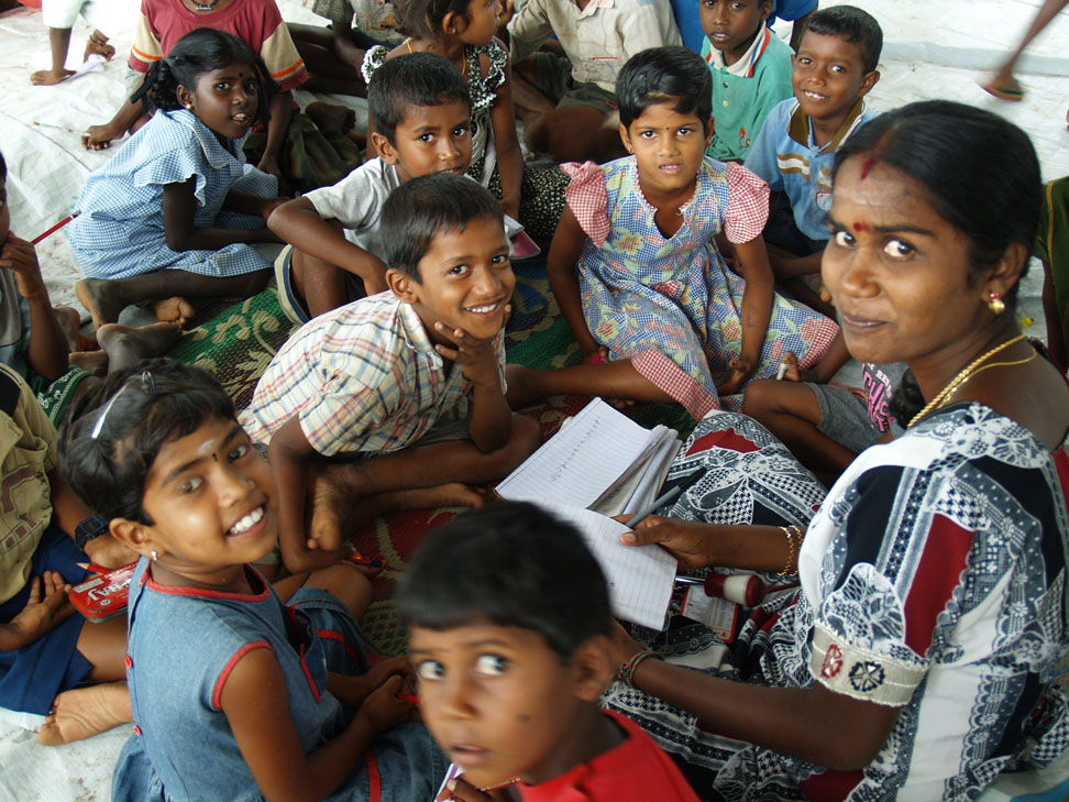 A volunteer teacher helps children with their studies at a child-friendly space in the Kiliveddy Transit Centre for IDP families in Mutter Division, Trincomolee District, Sri Lanka, April 2007.The armed conflict between the Sri Lankan government and the L