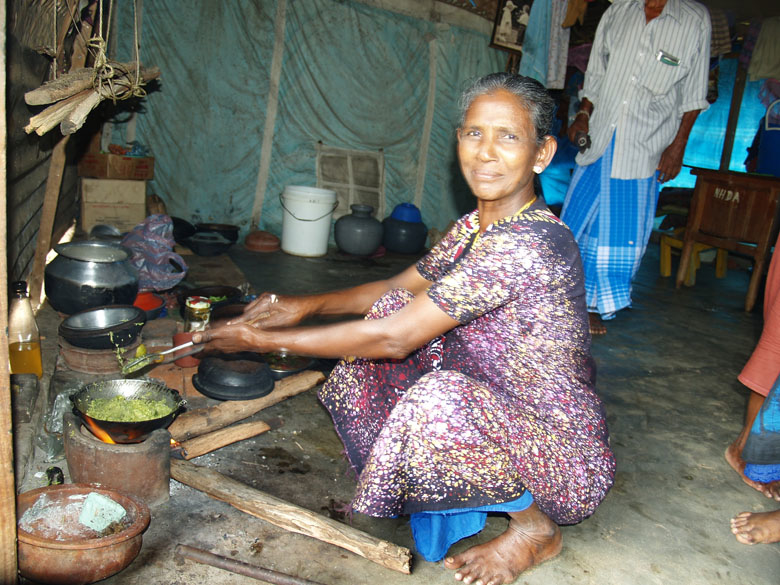 An Internally Dispalced Person (IDP), recently returned from Batticaloa District, prepares a meal in a shelter area at the transit center in Kiliveddy, Tricomalee District, Sri Lanka, April 2007.