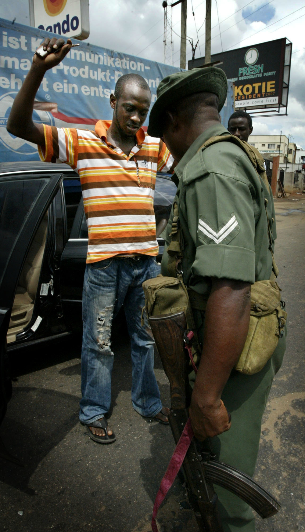A soldier searches a  civilian car in Lagos,  Nigeria, April 2007. Nigeria's recent  election results proclaiming a landslide victory for the People's Democratic Party and their presidential candidate, Umaru Musa Yar' Adua, have been met  by a deafening s