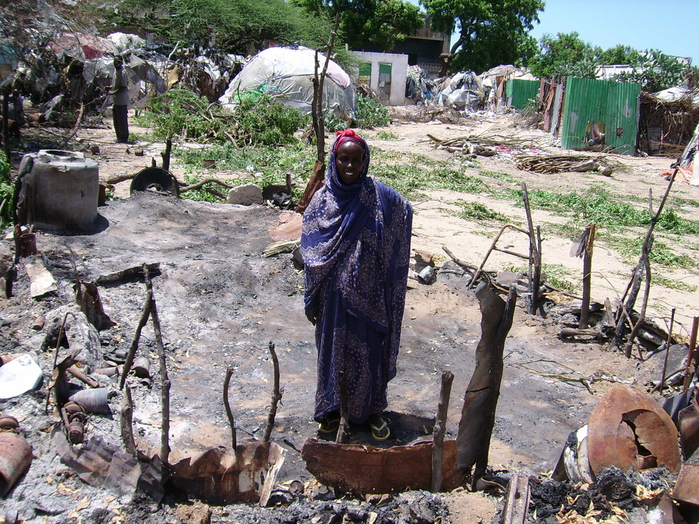 One of the IDPs stands in an area property was destroyed due to conflicts, Mogadishu, Somalia, May 2007. Conflict-related displacement in Somalia has forced people to leave their lands several times.